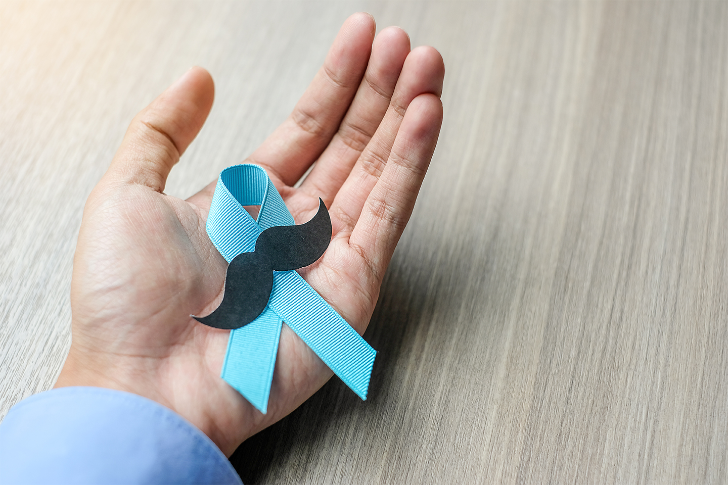 Prostate Cancer Awareness, light Blue Ribbon with mustache on wooden background for supporting people living and illness. Men Healthcare and World cancer day concept
